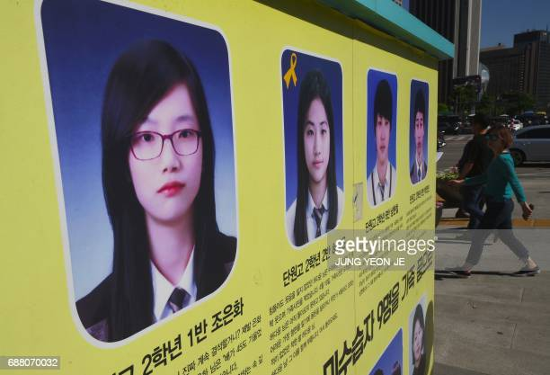 Pedestrians walk past portraits of Cho EunHwa one of four students who went missing in the 2014 South Korea's Sewol ferry disaster and other missing...
