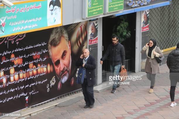 Pedestrians walk past portraits of slain Iranian military commander Qasem Soleimani in a main thoroughfare of the Iranian capital Tehran on January 4...