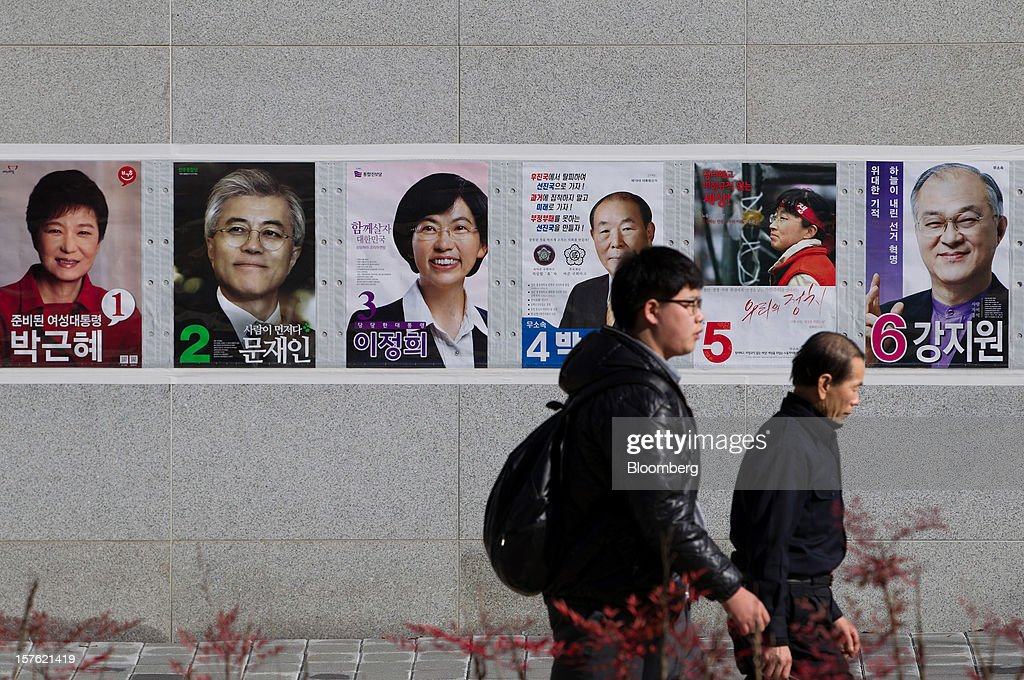 Pedestrians walk past posters of presidential candidates in Sejong, South Korea, on Tuesday, Dec. 4, 2012. The construction of Sejong City 120 kilometers (75 miles) south of the capital fulfills the vision of the late President Roh Moo Hyun, who pledged to reduce the dominance of Seoul and pump money into a region courted for its swing voters. Photographer: SeongJoon Cho/Bloomberg via Getty Images