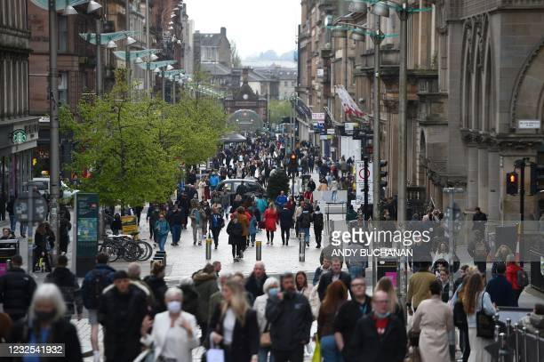 Pedestrians walk past re-opened shops and businesses in Glasgow on April 26, 2021 following the relaxing of some Covid-19 restrictions in Scotland,...