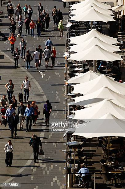 Pedestrians walk past restaurants along the promenade at East Circular Quay in Sydney Australia on Tuesday Oct 23 2012 Treasurer Wayne Swan on Monday...