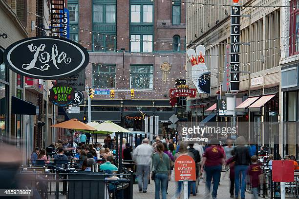 Pedestrians walk past restaurants and shops on East 4th Street in downtown Cleveland Ohio US on Saturday April 12 2014 Demand for manufactured...