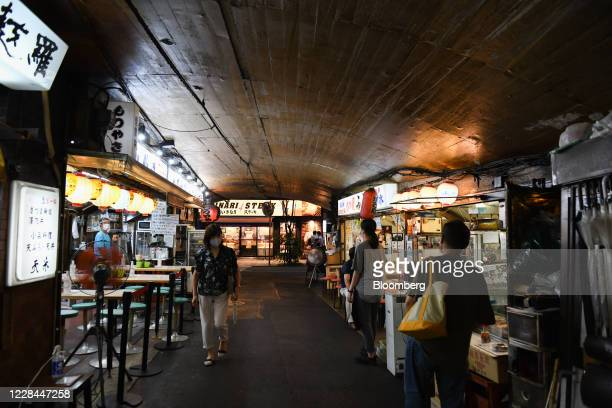 Pedestrians walk past restaurants and stores built under railway tracks in Tokyo, Japan, on Thursday, Sept. 3, 2020. In Tokyo, the spaces beneath...