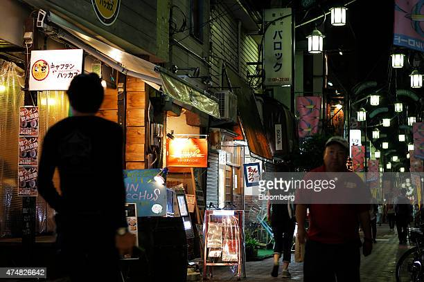 Pedestrians walk past restaurants at night in the Koenji district of Tokyo Japan on Sunday May 24 2015 Japan's Topix index fell for the first time in...