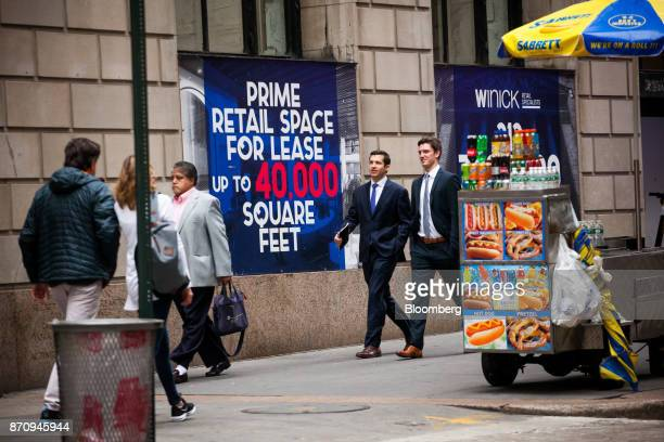 Pedestrians walk past retail space for lease signs along Wall Street near the New York Stock Exchange in New York US on Monday Nov 6 2017 Stocks rose...