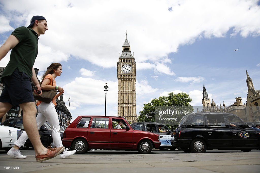 Pedestrians walk past rows of London taxi cabs parked outside Big Ben and the Houses of Parliament, during a protest against Uber Technologies Inc.'s car sharing service in London, U.K., on Wednesday, June 11, 2014. Traffic snarled in parts of Madrid and Paris today, with a total of more than 30,000 taxi and limo drivers from London to Berlin blocking tourist centers and shopping districts. Photographer: Simon Dawson/Bloomberg via Getty Images