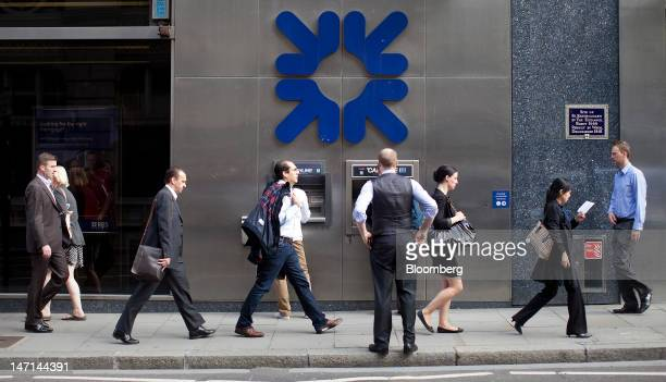 Pedestrians walk past Royal Bank of Scotland Group Plc automated teller machines outside a bank branch in London UK on Tuesday June 26 2012 Royal...