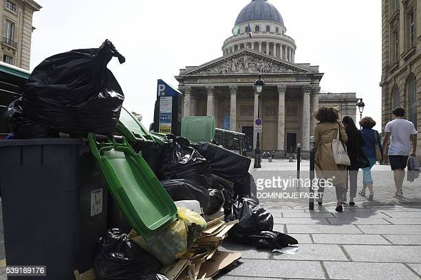 Pedestrians walk past rubbish bins on the pavement near the Pantheon in Paris on June 10 2016 The piles of uncollected household rubbish accumulating...