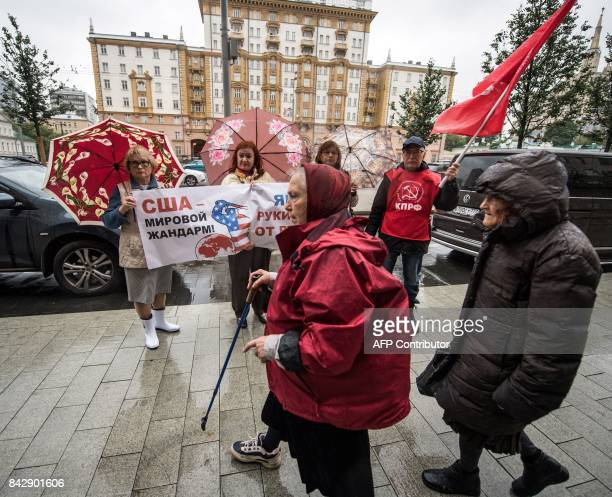 Pedestrians walk past Russian communist party supporters as they hold a poster reading 'USA is a policeman of the world' during a rally against US...