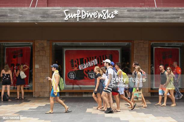 Pedestrians walk past sale signs displayed in a store window in the Manly Corso retail area in Sydney Australia on Friday Jan 5 2018 The Australian...