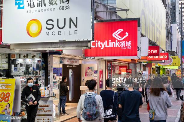 Pedestrians walk past several telecommunication corporations, Sun Mobile, Citylink, Vodaphone stores in Hong Kong.