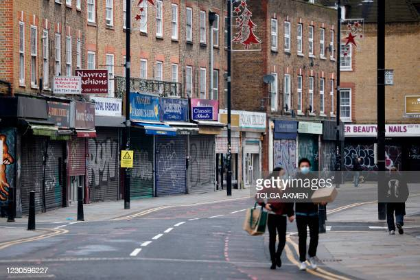 Pedestrians walk past shuttered shops along a near-deserted street in the City of London on January 15 during the third coronavirus lockdown. -...
