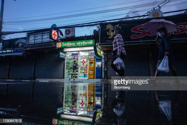 Pedestrians walk past shuttered stores at Bangla Road in Patong, Phuket, Thailand, on Saturday, Dec. 19, 2020. The tepid response to Thailands highly...