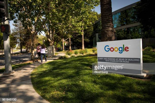 Pedestrians walk past signage at Google Inc headquarters in Mountain View California US on Wednesday April 25 2018 Alphabet Inc is pushing efforts to...