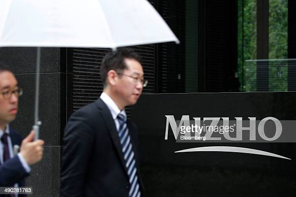 Pedestrians walk past signage bearing the corporate logo of Mizuho Financial Group Inc displayed outside the Otemachi Tower which houses the head...