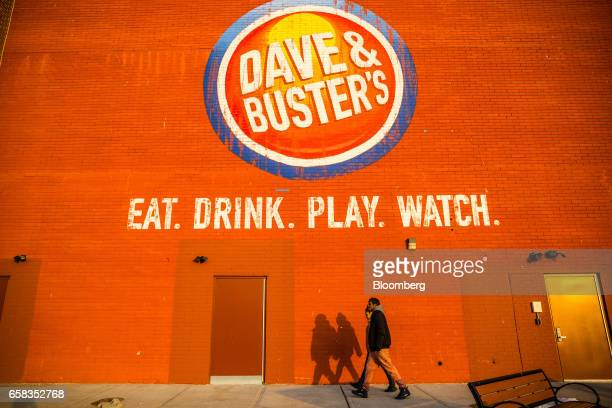 Pedestrians walk past signage for a Dave & Buster's Entertainment Inc. Location in Pelham, New York, U.S. On Friday, March 24, 2017. Dave & Buster's...