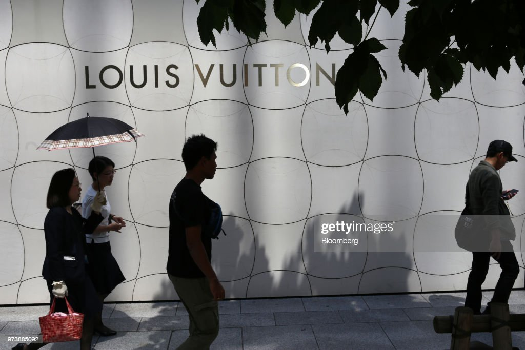 Pedestrians walk past signage for Louis Vuitton, operated by LVMH Moet Hennessy Louis Vuitton SE, in the Ginza district of Tokyo, Japan, on Sunday, May 28, 2018. The savings-rich elderly spend about 9.7 trillion yen ($87 billion) a year on their offspring and such spending last year accounted for about a third of the modest growth in total consumption, according to Hiromichi Shirakawa, chief Japan economist at Credit Suisse Group. Photographer: Takaaki Iwabu/Bloomberg via Getty Images
