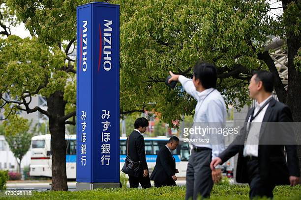 Pedestrians walk past signage for Mizuho Bank Ltd displayed outside a branch in Tokyo Japan on Tuesday May 12 2015 Mizuho Financial Group Inc is...