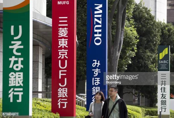 Pedestrians walk past signage for Resona Bank Ltd from left Bank of TokyoMitsubishi UFJ Ltd Mizuho Bank Ltd and Sumitomo Mitsui Banking Corp in Tokyo...