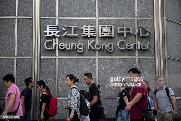 Pedestrians walk past signage for the Cheung Kong Center in Hong Kong on August 11 2016 Billionaire Hong Kong businessman Li Kashing on August 11 saw...