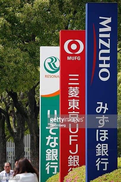 Pedestrians walk past signs for Mizuho Bank Ltd right Bank of Tokyo Mitsubishi UFJ Ltd center and Resona Bank Ltd in Tokyo Japan on Tuesday May 13...