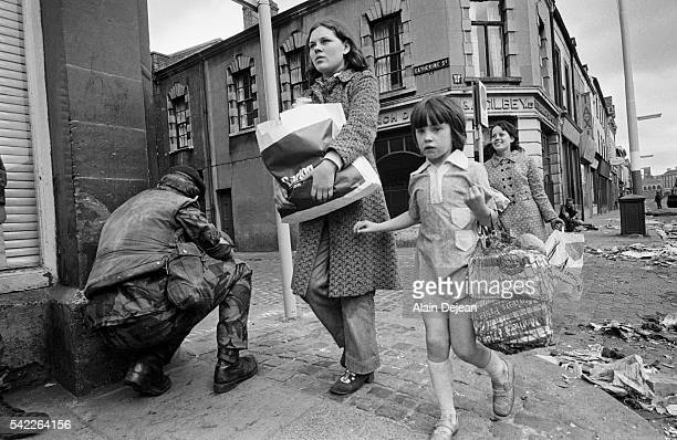 Pedestrians walk past soldiers crouched on a street corner while patrolling the streets after conflicts broke out in Belfast Northern Ireland in...