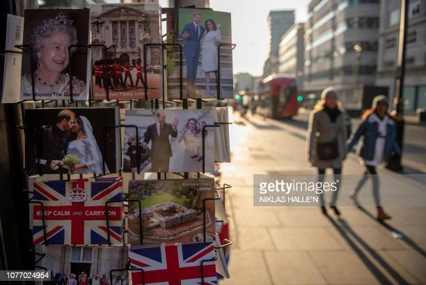 Pedestrians walk past souvenirs including postcards depicting members of Britain's Royal Family in central London on January 4 2019 British lawmakers...