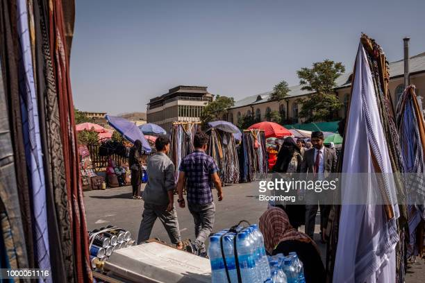 Pedestrians walk past stall vendors at a street market in Kabul Afghanistan on Thursday July 12 2018 US President Donald last year said 16000 US...