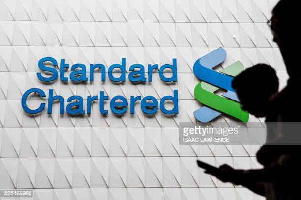 Pedestrians walk past Standard Chartered signage in the Central district of Hong Kong on August 2 2017 Standard Chartered's halfyear results will be...