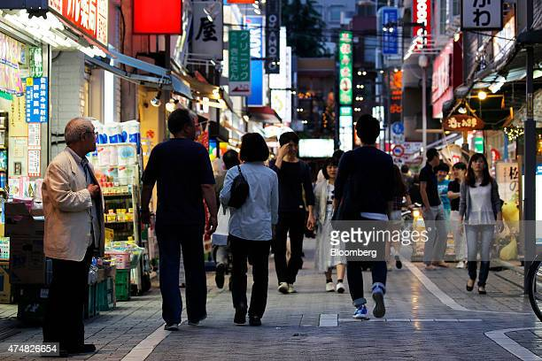 Pedestrians walk past stores and restaurants at dusk in the Koenji district of Tokyo Japan on Sunday May 24 2015 Japan's Topix index fell for the...