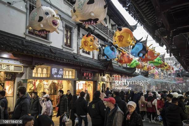 Pedestrians walk past stores as Chinese zodiacthemed paper lanterns are displayed at the Yuyuan Garden ahead of the Lunar New Year in Shanghai China...