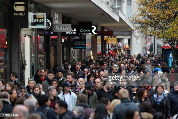 Pedestrians walk past stores as they walk along Oxford Street in London on November 24 2017 Black Friday is a sales offer originating from the US...