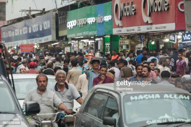 Pedestrians walk past stores displaying signage for GuangdongOppoElectronics Co and QMobile at the Karachi Mobile Market in Karachi Pakistan on...