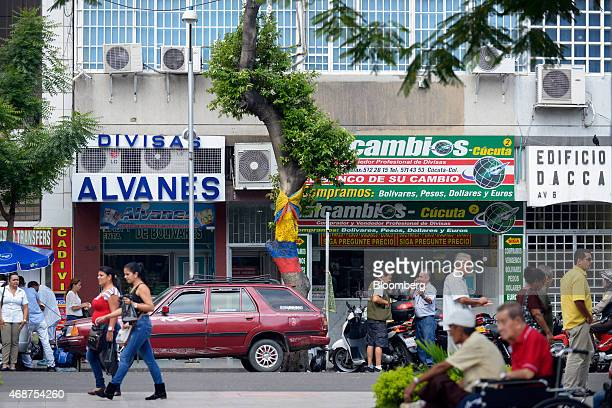 Pedestrians walk past stores near Santander Square, including a currency exchange shop, center right, in Cucuta, Colombia, on Tuesday, Feb. 24, 2015....