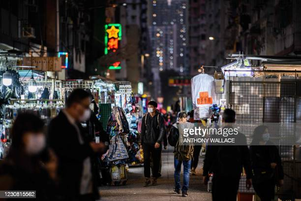 Pedestrians walk past street market stalls in the Sham Shui Po district of Kowloon in Hong Kong on January 27 one of the international business hub's...