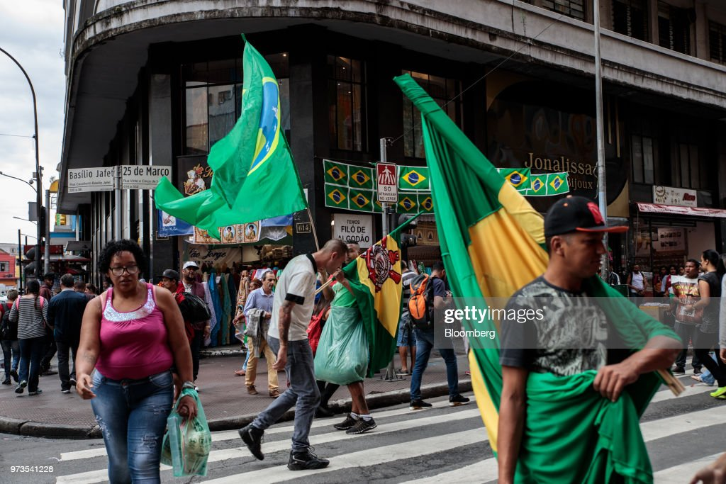 Pedestrians walk past street vendors selling Brazilian flags ahead of the FIFA World Cup games in downtown Sao Paulo, Brazil, on Wednesday, June 13, 2018. In a curious quirk of Brazil's electoral calendar, for the last 28 years Latin America's largest economy has gone to the polls shortly after the World Cup. In the football-obsessed country, politicians have long attempted to hijack the sport to burnish their image. Photographer: Patricia Monteiro/Bloomberg via Getty Images