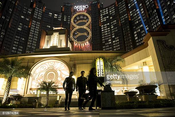 Pedestrians walk past Studio City casino resort developed by Melco Crown Entertainment Ltd illuminated at night in Macau China on Tuesday Feb 16 2016...