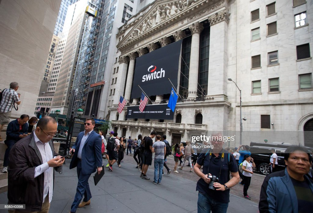 Pedestrians walk past Switch Inc. signage displayed outside of the New York Stock Exchange (NYSE) during the company's initial public offering (IPO) in New York, U.S., on Friday, Oct. 6, 2017. Switchjumped by almost half in its trading debut after raising $531 million in an initial public offering, the third-biggest technology IPO this year in the U.S.. Photographer: Michael Nagle/Bloomberg via Getty Images