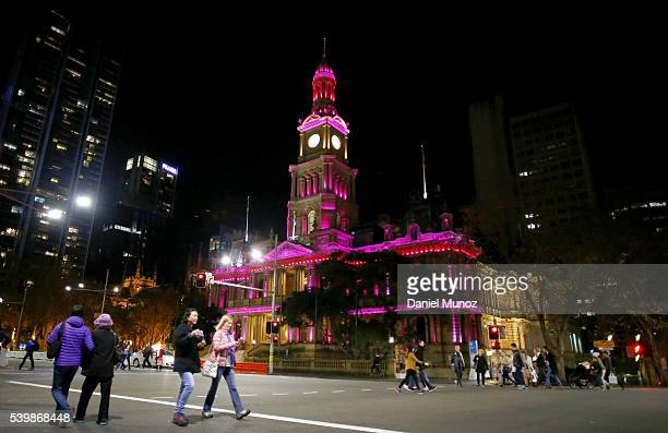 Pedestrians walk past Sydney Town Hall which is illuminated pink to remember victims of the Orlando night club massacre on June 13, 2016 in Sydney,...