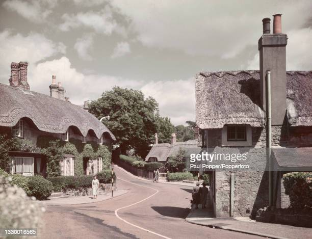 Pedestrians walk past thatched cottages lining a road in Shanklin Old Village, a seaside resort on the Isle of Wight, England circa 1950.