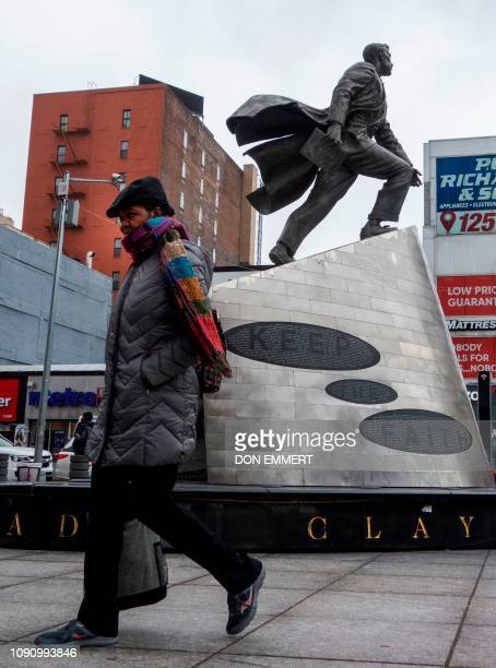 Pedestrians walk past the Adam Clayton Powell Jr monument on 125th street bundled against the cold January 29 2019 in New York The polar vortex is...