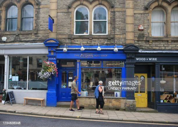 Pedestrians walk past The Afghan Rug Shop on the high street in Hebden Bridge, northern England, on August 20, 2021. - Overseas businesses selling...