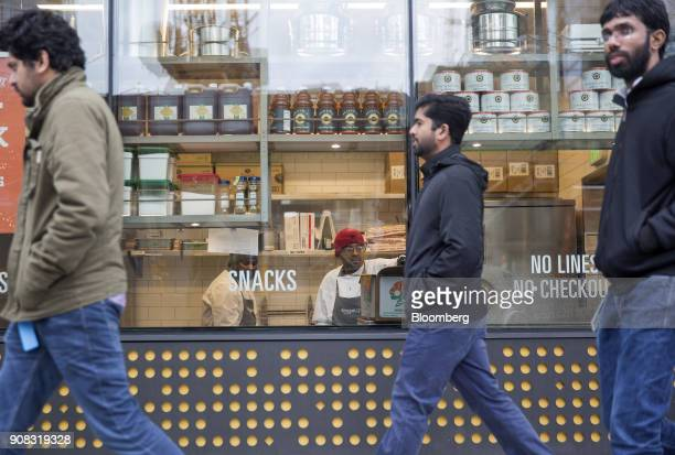 Pedestrians walk past the Amazon Go store in Seattle Washington US on Wednesday Jan 17 2018 After more than a year of testing with an employeeonly...