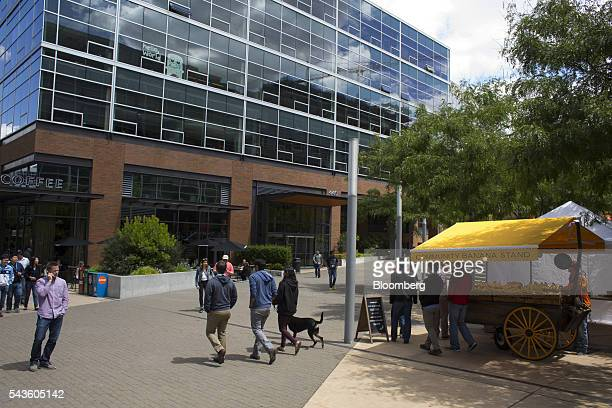 Pedestrians walk past the Amazoncom Inc headquarters in the South Lake Union neighborhood of Seattle Washington US on Wednesday June 15 2016 In 2010...