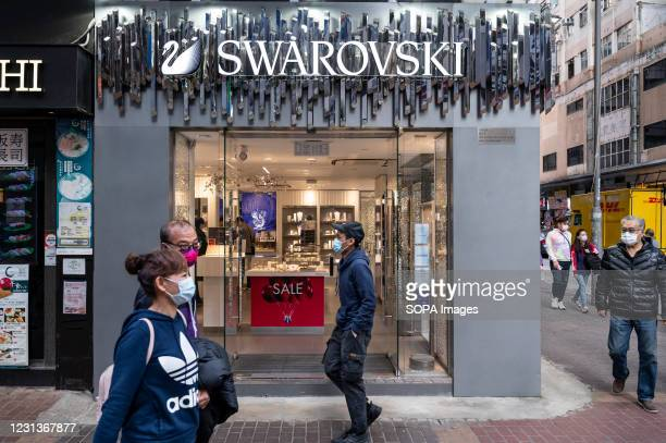 Pedestrians walk past the Austrian jewellery producer and luxury brand Swarovski store seen in Hong Kong.