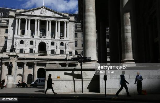 Pedestrians walk past the Bank of England and the Royal Exchange in the City of London on July 31 2017 Lastminute talks with staff at the Bank of...