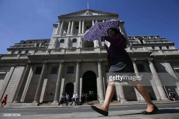 Pedestrians walk past the Bank of England in the City of London on August 2 2018 The Bank of England hiked interest rates on August 2 by a...