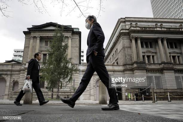 Pedestrians walk past the Bank of Japan headquarters in Tokyo, Japan, on Monday, March 16, 2020. The Bank of Japan strengthened stimulus but stopped...
