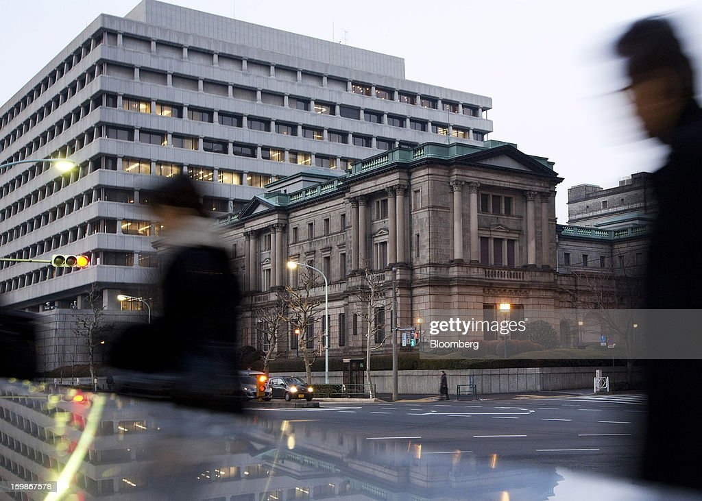 Pedestrians walk past the Bank of Japan headquarters in Tokyo, Japan, on Tuesday, Jan. 22, 2013. The Bank of Japan set a 2 percent inflation target and said it will shift to Federal Reserve-style open-ended asset purchases in its strongest commitment yet to ending two decades of deflation. Photographer: Tomohiro Ohsumi/Bloomberg via Getty Images