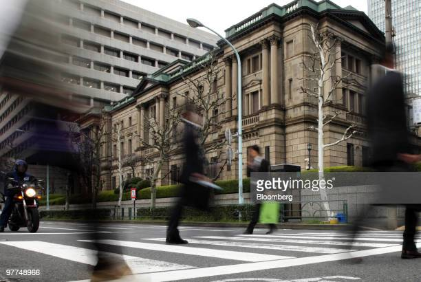 Pedestrians walk past the Bank of Japan headquarters in Tokyo, Japan, on Tuesday, March 16, 2010. Investors have become more confident that central...